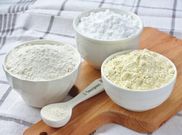 Drei schalen mit glutenfreiem mehl - reismehl, hirsemehl und kartoffelstärke und löffel mit xanthangummi