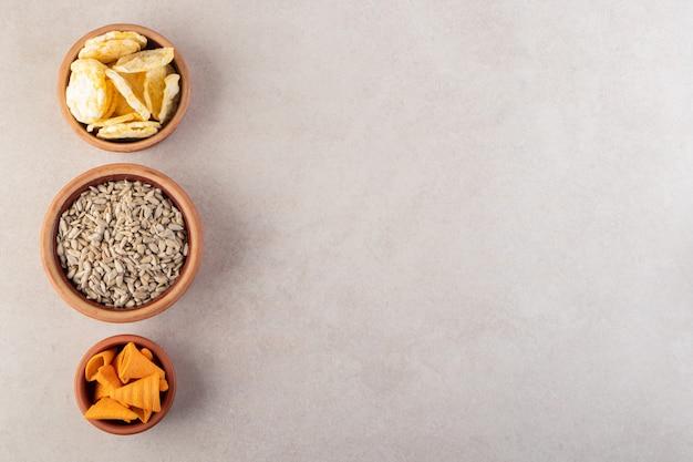 Drei schalen mit pommes, crackern und sonnenblumenkernen auf steinoberfläche.