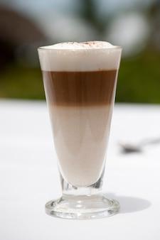 Drei schaumiger schaumiger kaffee in einem glasbecher