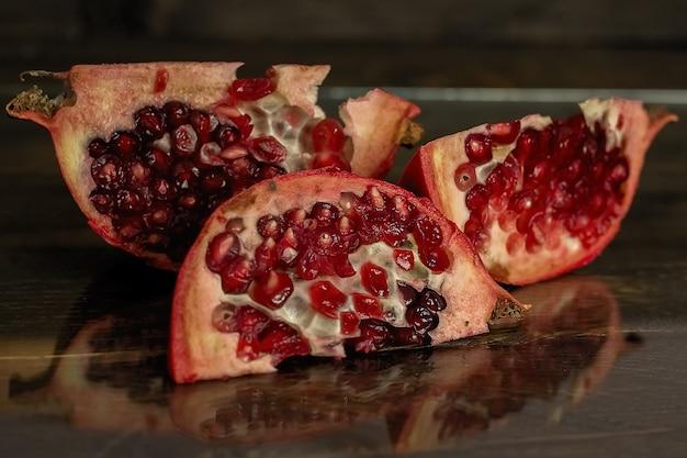 Drei scheiben des geschnittenen granatapfels liegen auf einem holzbrett.