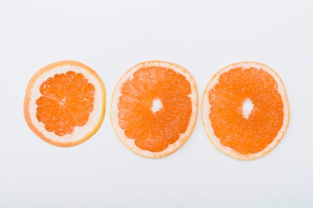 Drei scheiben orange vereinbarten in der reihe auf weißem hintergrund