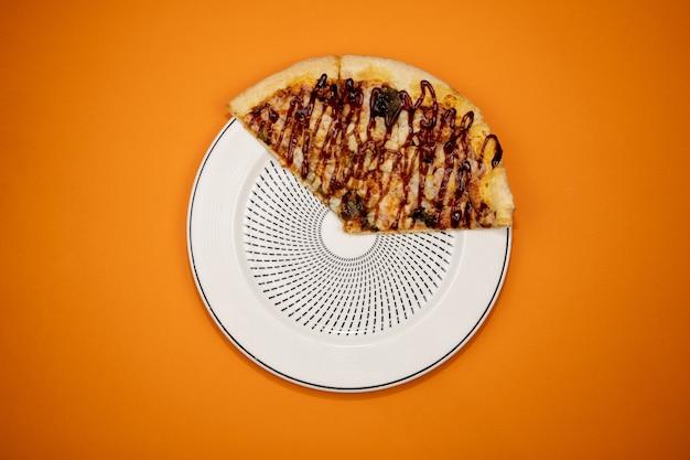 Drei scheiben pizza auf einem teller und orange