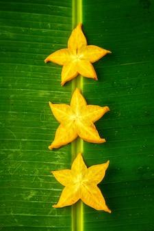 Drei scheiben reifer gelber sternfrucht carambola oder sternapfel (starfruit) auf grünem bananenblatt, vertikale zusammensetzung