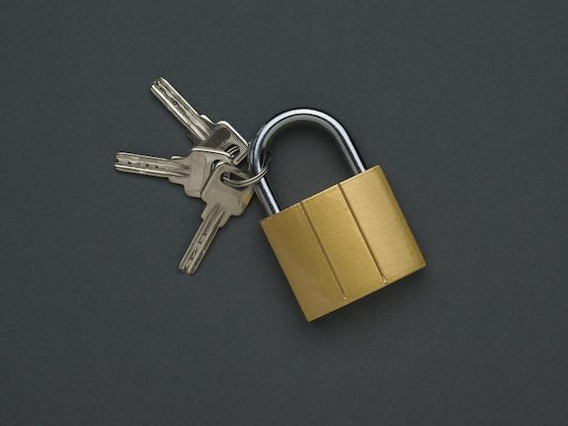 Drei schlüssel mit geschlossenem schloss. das konzept von schutz und sicherheit. flach liegen.