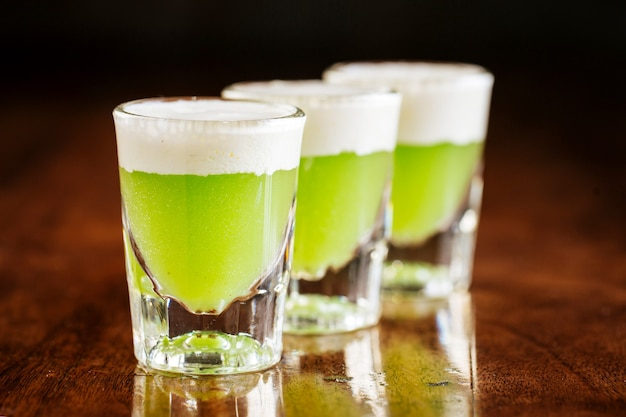 Drei schnapsgläser mit grünen alkoholischen cocktails