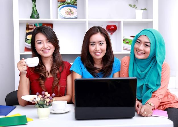 Drei schöne college-studenten lächeln und studieren zusammen im wohnzimmer