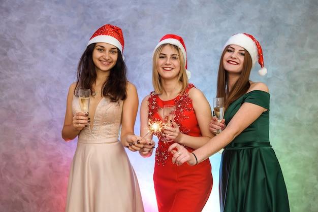 Drei schöne frauen, die auf neujahrsparty mit champagnergläsern anstoßen