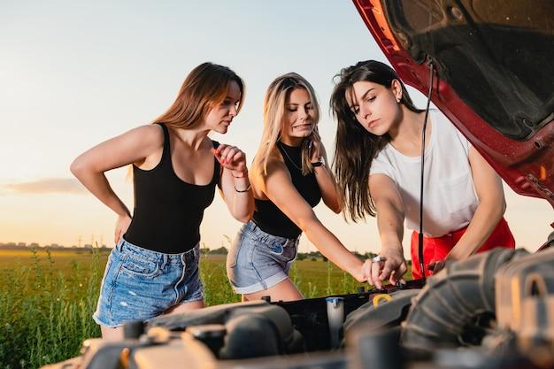 Drei schöne frauen stecken während des roadtrips fest, versuchen das fahrzeug zu reparieren, schauen auf die offene motorhaube und fahren abenteuer