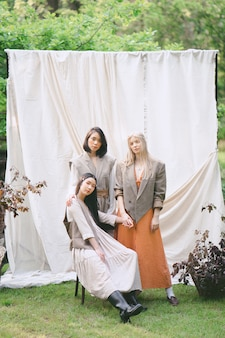 Drei schöne frauen stehen, sitzen und schauen im garten.