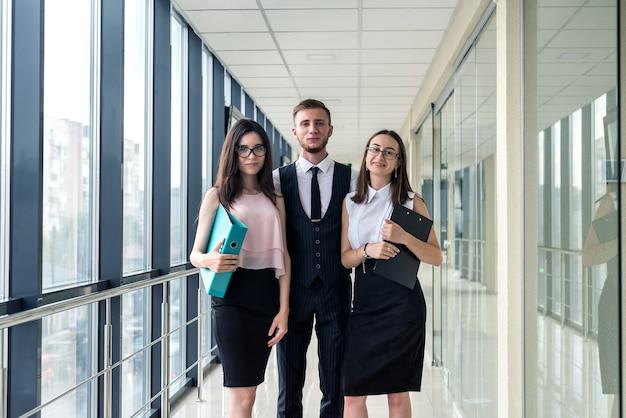 Drei schöne geschäftspartner diskutieren papierkram im modernen büroflur. tagungskonzept