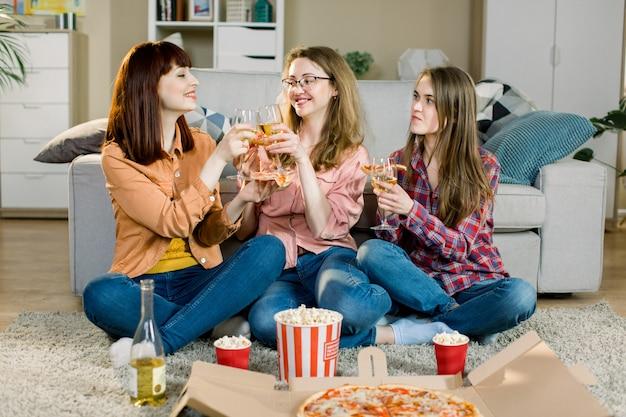 Drei schöne junge frauen, die wein trinken und zu hause pizza essen. glückliche schöne freunde lachen, essen pizza zu hause party. frau, die zusammen zu abend isst und mahlzeit genießt. freizeit, freundschaft