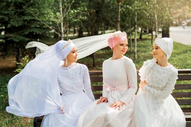 Drei schöne junge frauen in festlichen muslimischen kleidern
