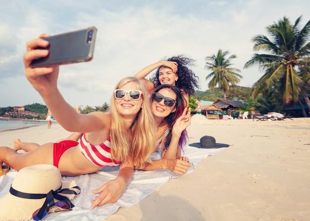 Drei schöne junge schlanke europäische freundinnen in leuchtend roten und gestreiften bikinis liegen auf dem sand, indem sie ein selfie auf einem smartphone an einem tropischen strand im urlaub, glücksfreude sommer und spaß machen