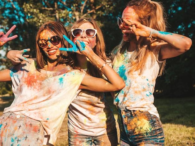 Drei schöne lächelnde mädchen, die auf holi party aufwerfen