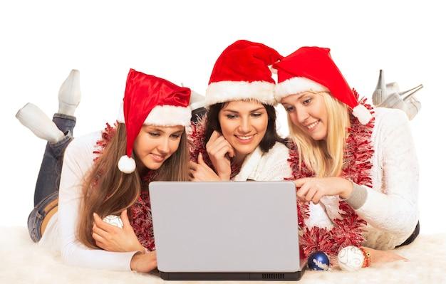 Drei schöne mädchen am silvesterabend, die laptop betrachten