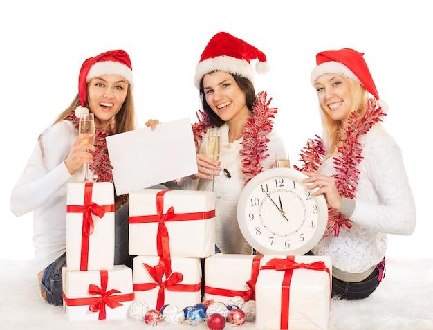 Drei schöne mädchen am silvesterabend sitzen mit uhr, geschenken, champagner