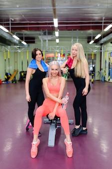Drei schöne mädchen, die im fitnessstudio aufwerfen.
