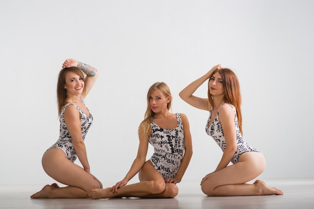 Drei schöne mädchen in badeanzügen stehen auf grauem hintergrund