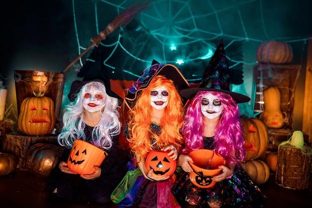 Drei schöne mädchen in einem hexenkostüm. lustige schwestern feiern den feiertag
