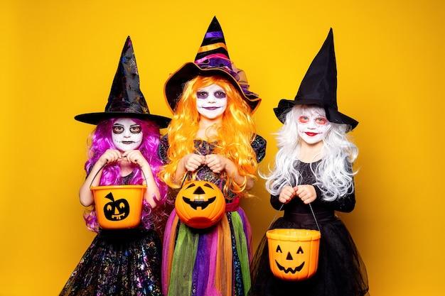 Drei schöne mädchen in einem hexenkostüm und in den hüten auf einem gelben hintergrund erschrecken und machen gesichter.