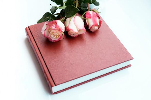 Drei schöne rosen liegen auf rotem leder bedecktem hochzeitsalbum oder hochzeitsbuch.