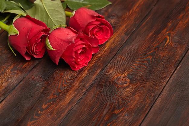 Drei schöne rote rosen auf holztisch, romantische oberfläche