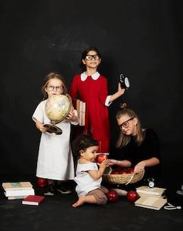 Drei schöne schülerinnen aus verschiedenen klassen und vorschuljunge auf einem schwarzen hintergrund