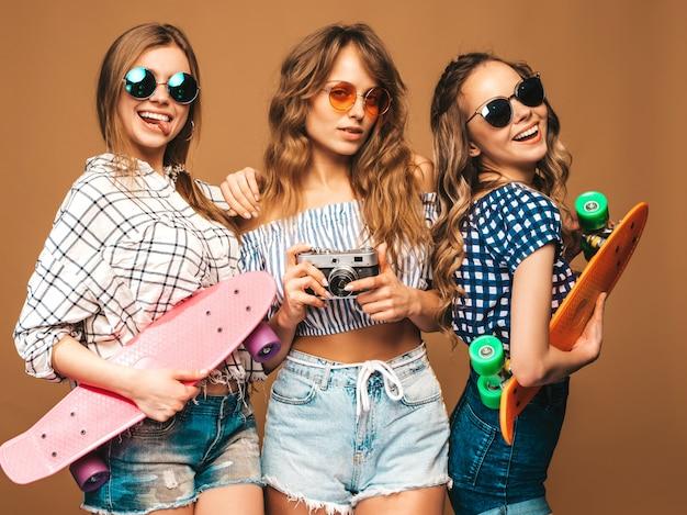 Drei schöne stilvolle lächelnde mädchen mit bunten pennyskateboards. frauen in der karierten hemdkleidungsaufstellung des sommers. fotografieren mit einer retro-fotokamera