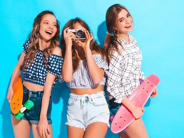 Drei schöne stilvolle lächelnde mädchen mit bunten pennyskateboards. frauen in sommerkleidung kariertes hemd. fotografieren mit einer retro-fotokamera