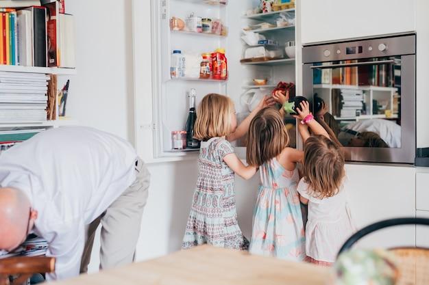Drei schöne weibliche kleinkind helfen ihrem vater beim auspacken von lebensmitteln