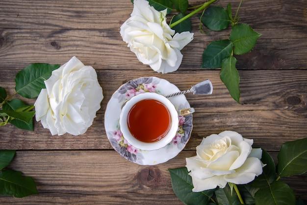 Drei schöne weiße rosen und eine tasse tee auf einem rustikalen hölzernen hintergrund