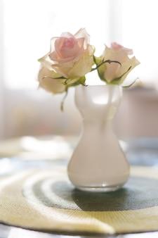 Drei schöne weiße und rosa rosen in der weißen mattvase auf dem tisch mit sonnenlicht