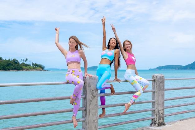 Drei schönheiten stehen auf dem pier und posieren in moderner kleidung für fitness.