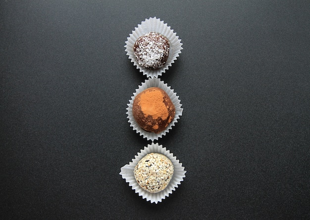 Drei schokoladen sind auf schwarzem hintergrund.