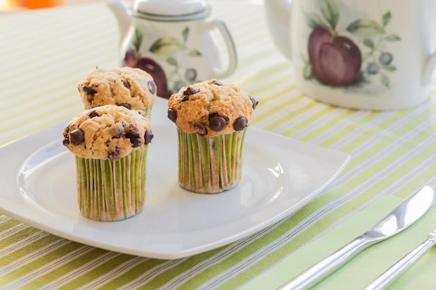 Drei schokoladenmuffins auf weißem teller und grün gestreifter tischdecke beim frühstück