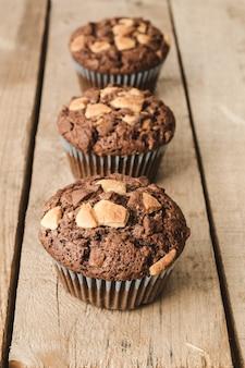 Drei schokoladenmuffins reihen sich aneinander.
