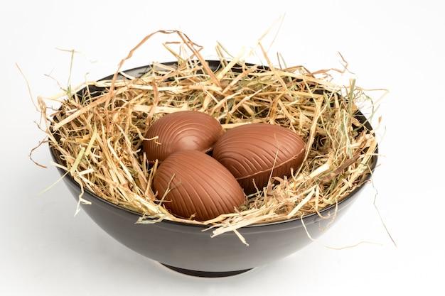 Drei schokoladenostereier im stroh in der schüssel