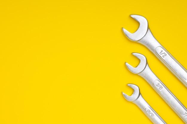 Drei schraubenschlüssel auf gelb mit platz für text und design