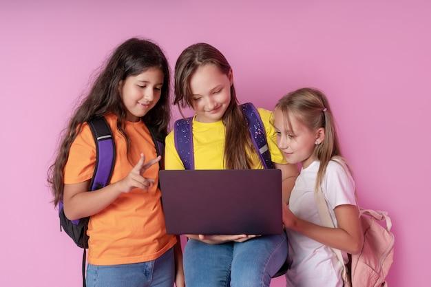 Drei schülerinnen schauen begeistert auf einen laptop laptop