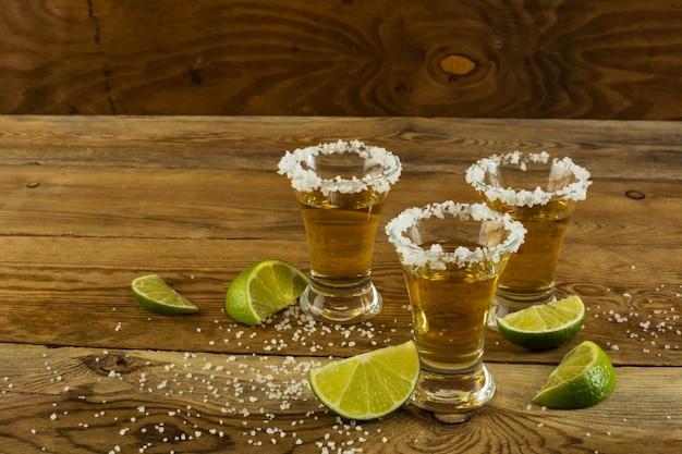 Drei schüsse goldtequila auf dem hölzernen hintergrund