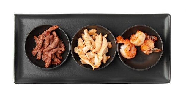 Drei schüsseln mit gekochten rinderhuhnscheiben und garnelen, isoliert auf weiss