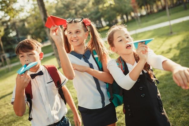 Drei schulkinder starten papierflugzeuge in den himmel und haben spaß in einem park in der nähe der schule