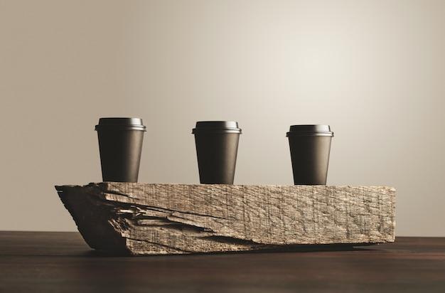 Drei schwarze pappbecher zum mitnehmen mit geschlossenen kappen, isoliert auf holzziegel auf tisch