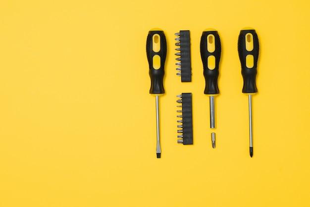 Drei schwarze und gelbe schraubendreher auf gelbem grund mit platz für text. werkzeuge, bau und werkstatt, reparaturen zu hause, slusararbeiten.