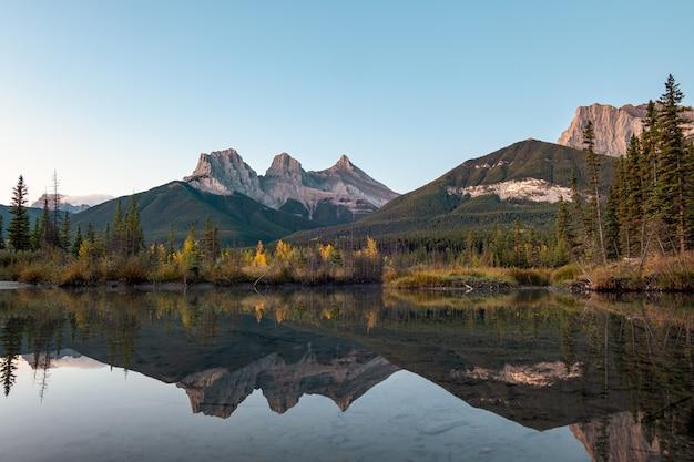 Drei schwestern berge von rocky mountains reflexion über bow river am morgen in canmore, banff nationalpark, kanada