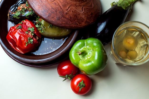 Drei schwestern dolma mit aubergine, tomate und paprika, serviert mit kompott