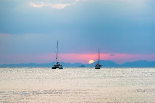 Drei segelyachten im meer bei sonnenuntergang geht die sonne über den bergen unter