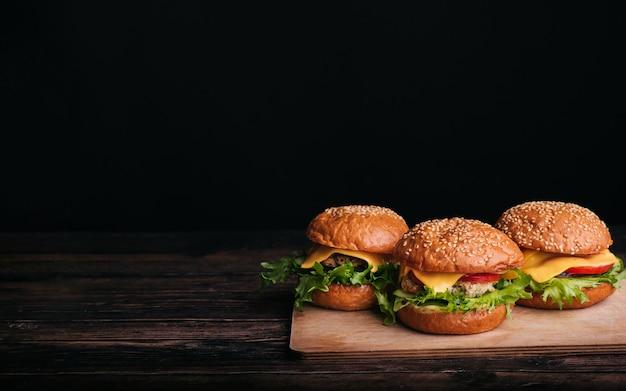 Drei selbst gemachte hamburger mit fleisch, käse, kopfsalat, tomate auf einem holztisch