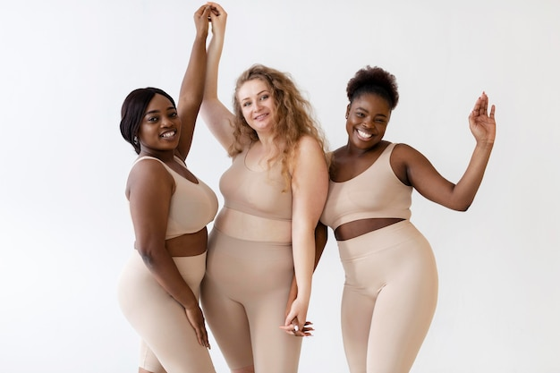 Drei selbstbewusste frauen, die zusammen posieren, während sie einen körperformer tragen