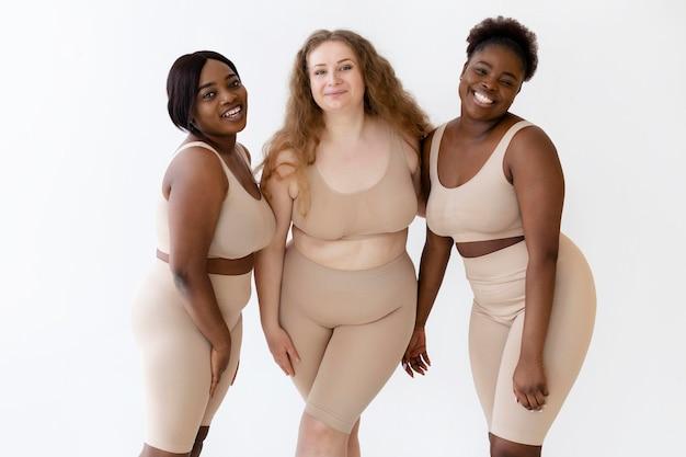 Drei selbstbewusste smiley-frauen posieren, während sie einen körperformer tragen